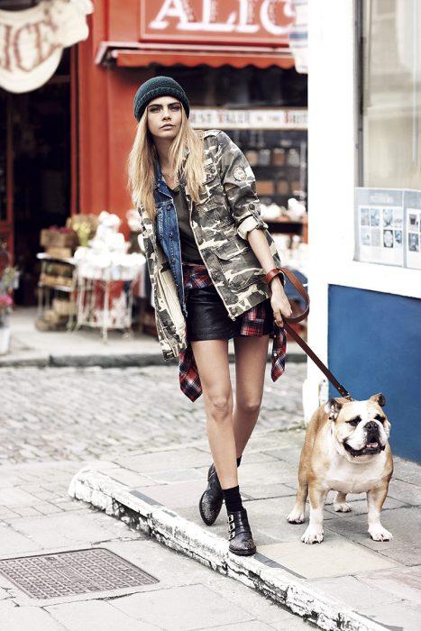 Cara delevinge caminando junto a su perro