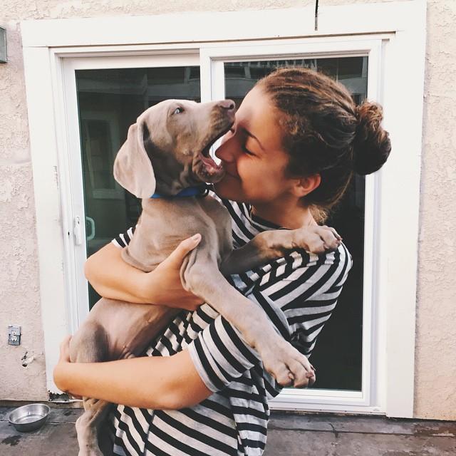 Chica abrazando a un perro que está abriendo el hocico
