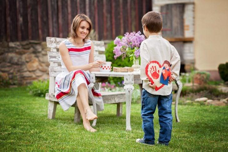 niño le lleva regalo sorpresa a mamá