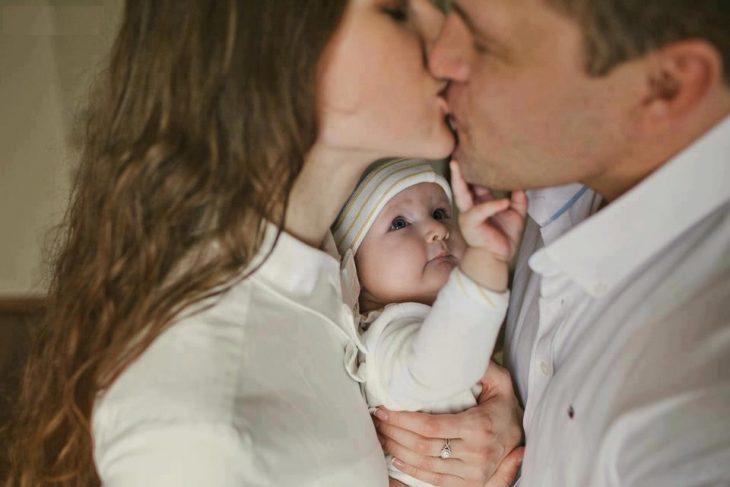 padres besándose con bebé en medio