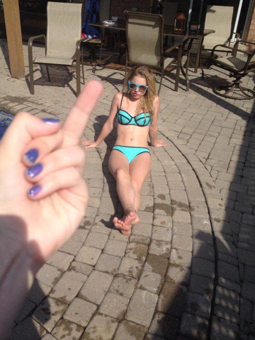mano con gesto obsceno y chica en bikini