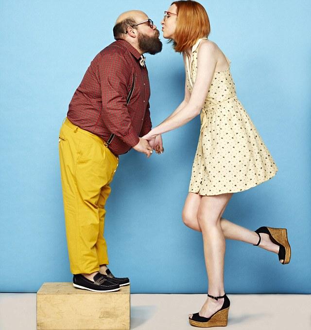 mujer alta besa hombre pequeño