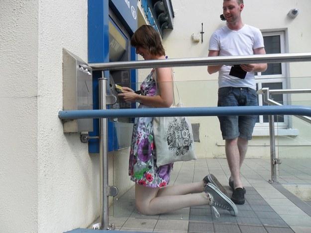 mujer muy alta agachada en cajero