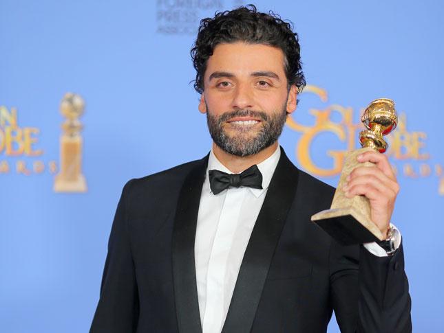 Oscar Issac sosteniendo un globo de oro