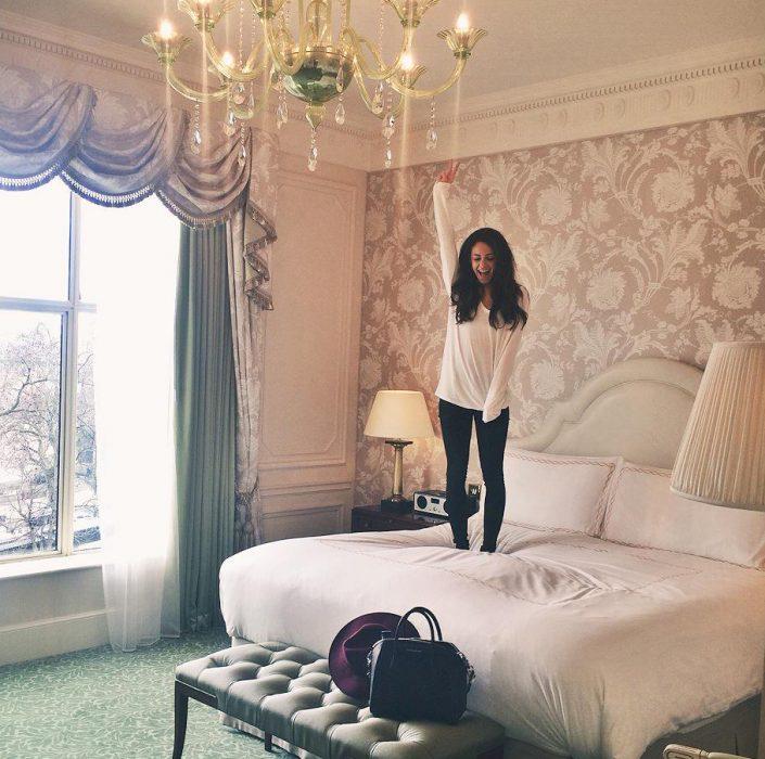 Chica brincando en la cama d un hotel