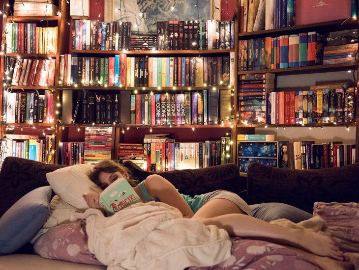 Chica recostada en la cama leyendo un libro