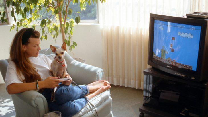 Chica jugando video juegos junto con un cachorro