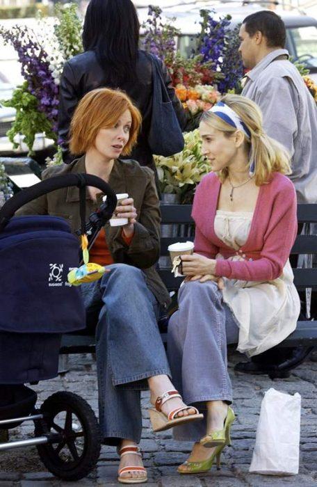 Escena de la serie sex and the city. Miranda y carrie sentadas en un parque conversando