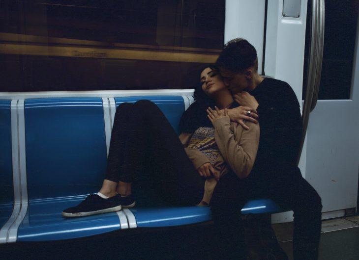 pareja en vagon metro abrazados