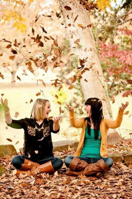 amigas jugando con hojas