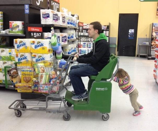 niña pequeña empujando cochecito de compras