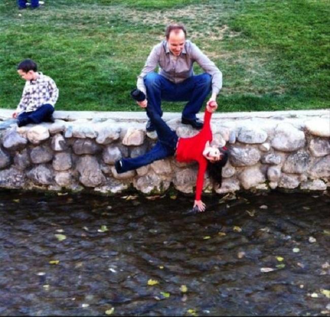 padre sostiene a niña para que toque el río