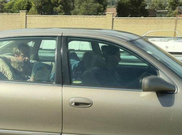 papá lee a hija pequeña en la parte trasera del carro