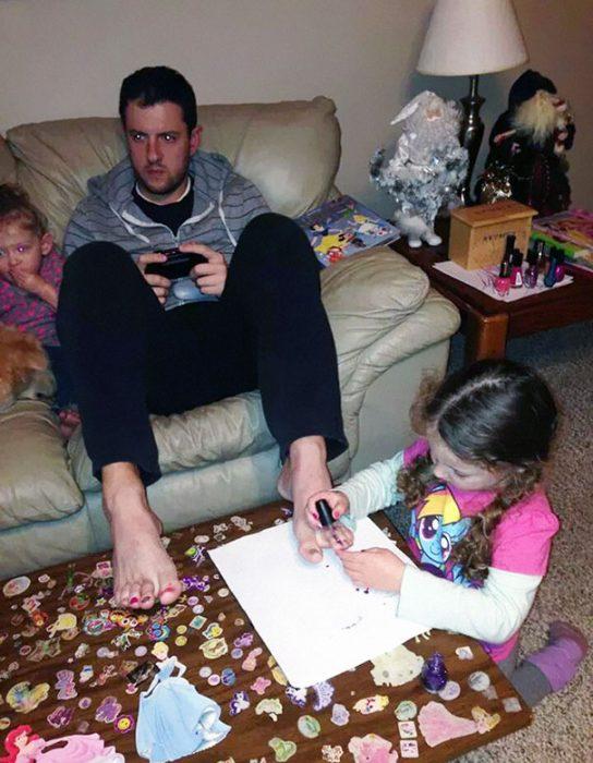 pequeña pintando uñas de los pies a papá mientras juega videojuegos