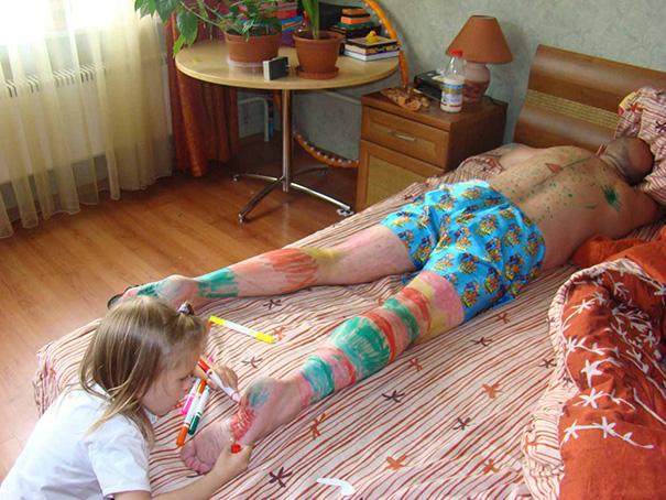 niña pintando a papá dormido