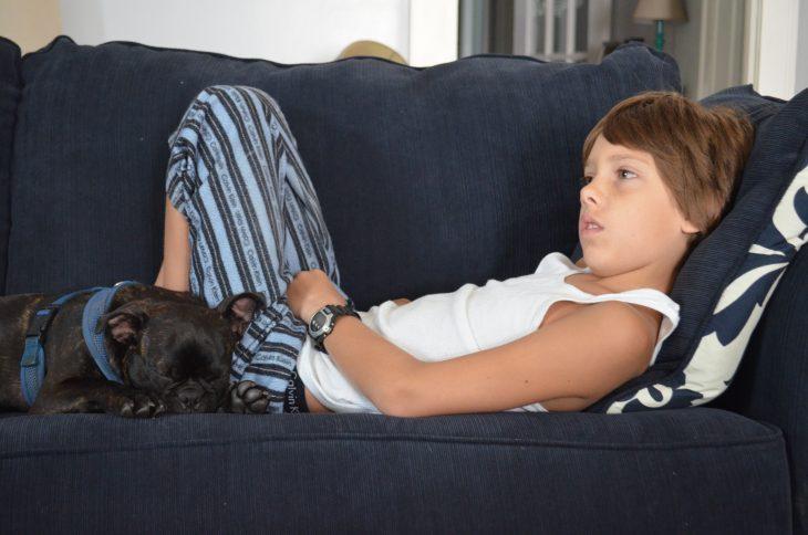 niño acostado en sillón con perro