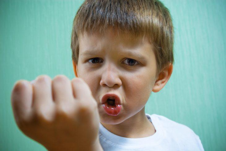 niño enojado con gesto amenazante