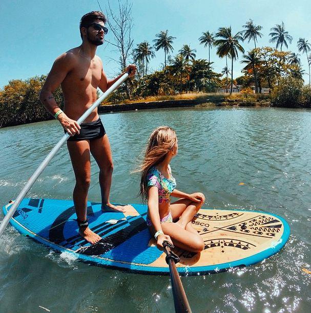 Pareja de novios sobre una tabla de surf tomándose una foto