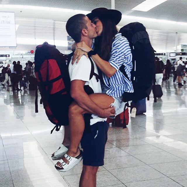Pareja de novios en el aeropuerto besándose