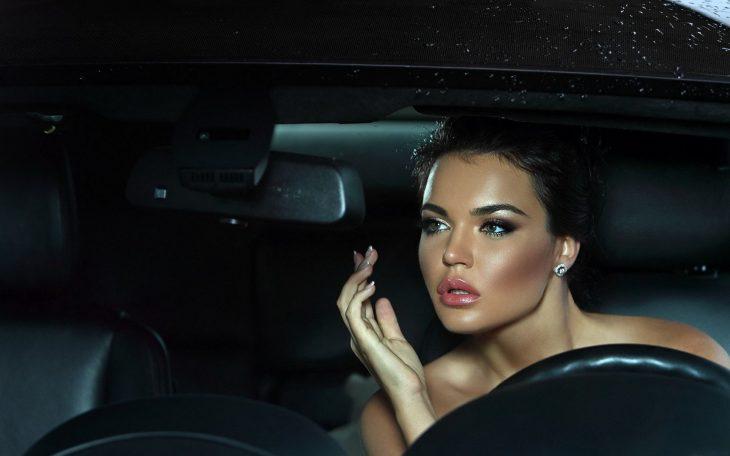 Chica maquillándose dentro de un auto