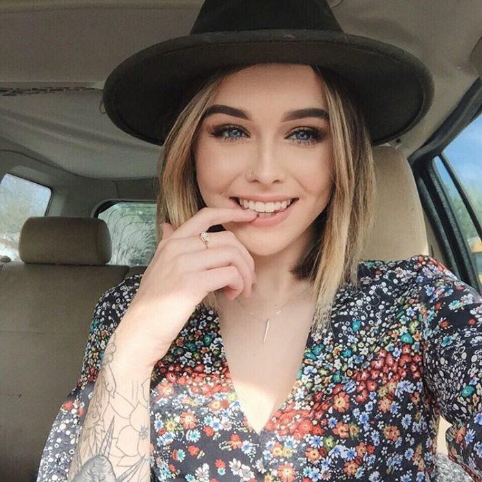 Chica usando un gorro y mordiendo su dedo mientras está en un automóvil