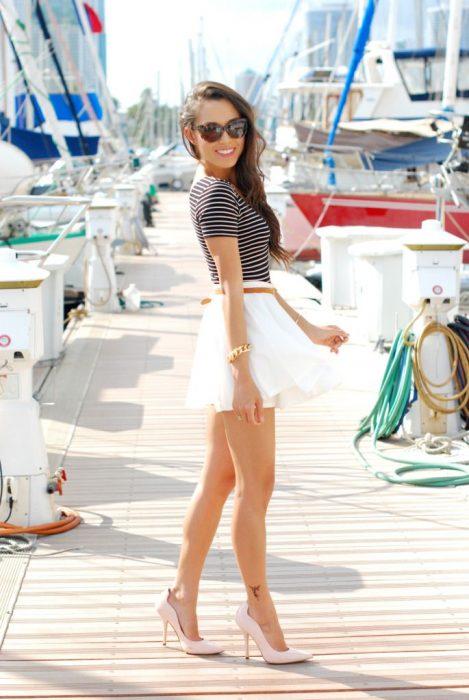 Chica en un muelle usando una falda blanca y camisa blanca a rayas