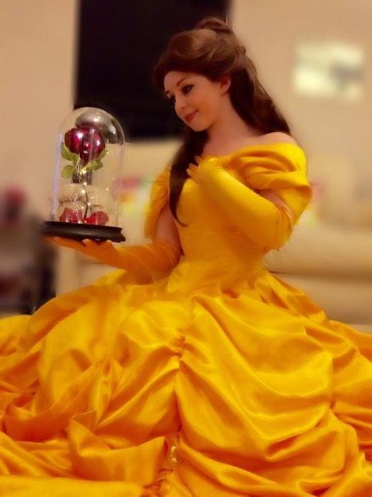Chica vestida como belle de la bella y la bestia sosteniendo una flor dentro de una capsula