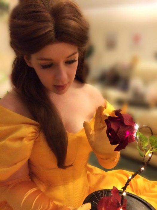 Chica caracterizada como belle de la bella y la bestia sosteniendo una rosa