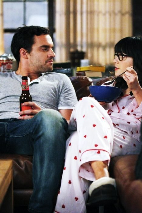 Escena de la serie new girl Nick y jess en el sofá en pijamas