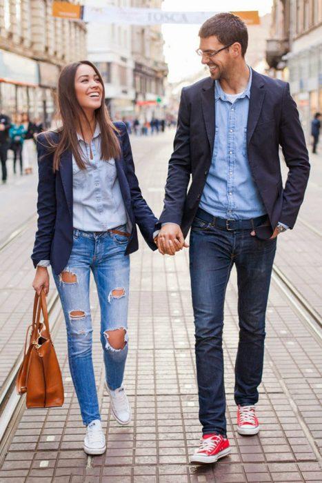Pareja de novios vestidos igual caminando por las calles tomados de las manos