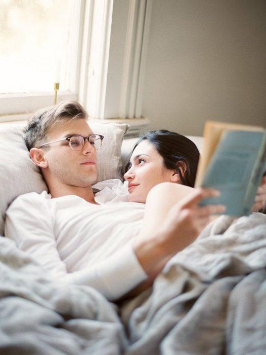Pareja de novios leyendo un libro mientras ambos están recostados