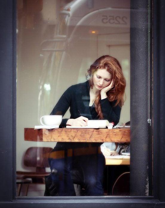 Chica sentada en un café mientras escribe un libro