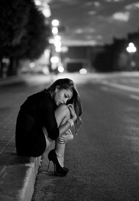 Chica sentada en la acera de una calle mientras se sujeta las manos con las rodillas