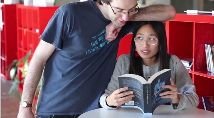 Hombre poniendo su brazo sobre la cabeza de una chica que está leyendo