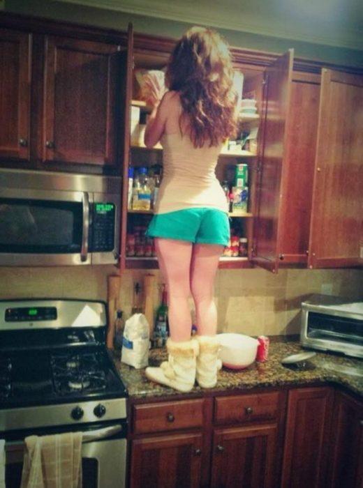 Chica chaparrita parada sobre la encimera de la cocina