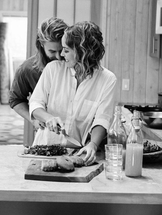 Chica cocinándole a un chico que la abraza