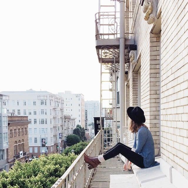 Chica sola sentada en la terraza de su casa viendo hacia el cielo