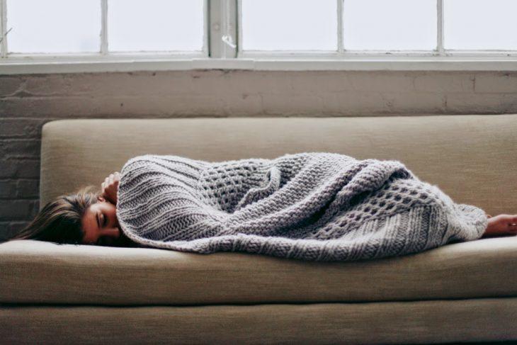 Chica recostada en un sofá tapad con una frasada