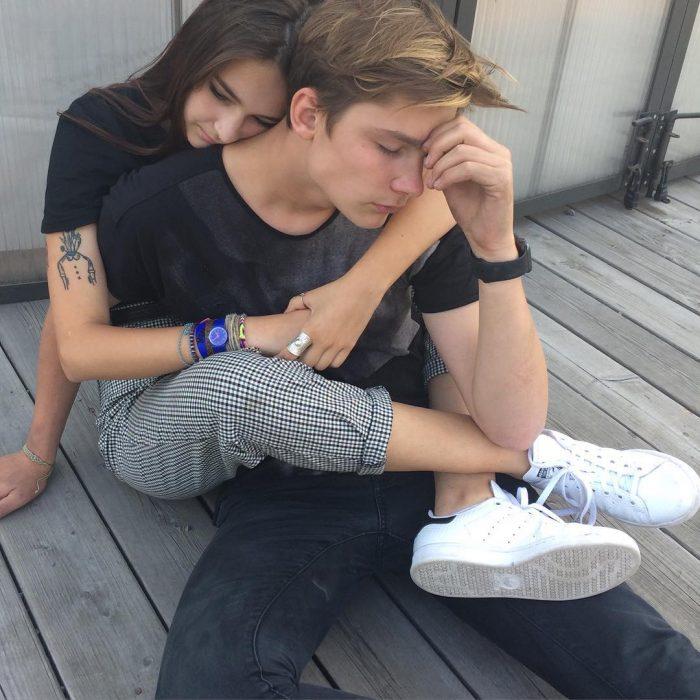 Pareja de novios abrazados mientras están sentados en el porche de una casa