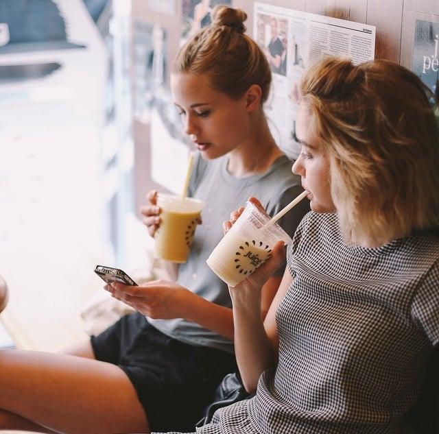 mejores amigas viendo un celular y tomando jugo