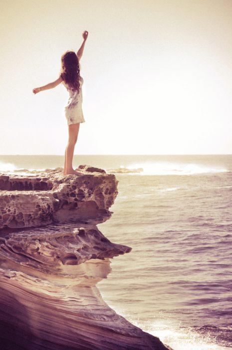 Chica parada en la orilla de un acantilado