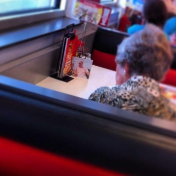 mujer come con fotografía de su esposo muerto