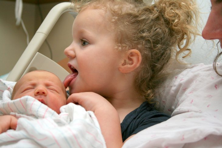 niña pasa la lengua por cara de su hermano recién nacido