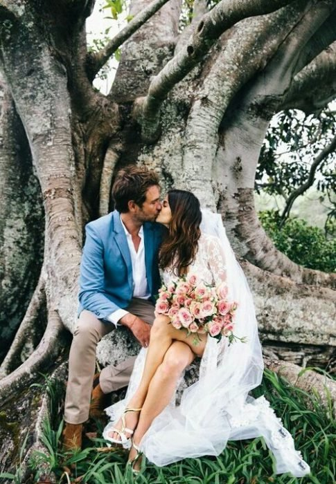 Pareja recién casada besándose en un árbol