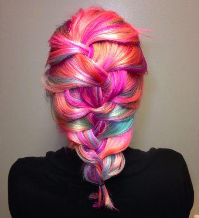 Chica con el cabello en distintos tonos de rosa sujetado en una trenza
