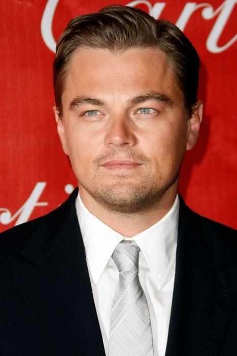 Leonardo DiCaprio usando un traje negro, una camisa blanca y una corbata en color gris
