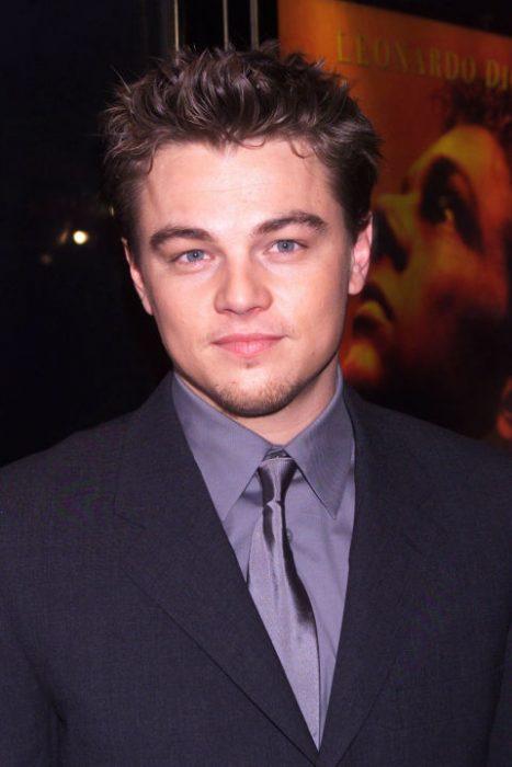 Leonardo DiCaprio usando un traje azul y una camisa morada en una red carpet del año 2000