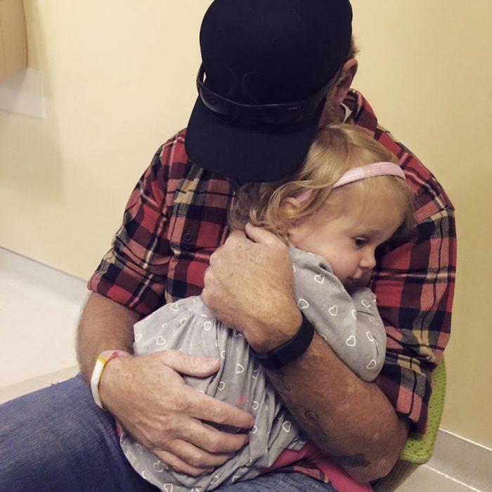 Papá abrazando a su hija que tiene cáncer