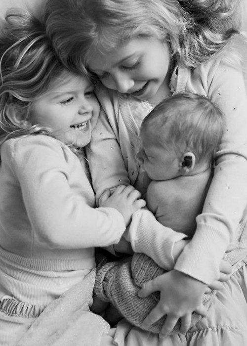 Hermanas abrazando a su hermano recién nacido