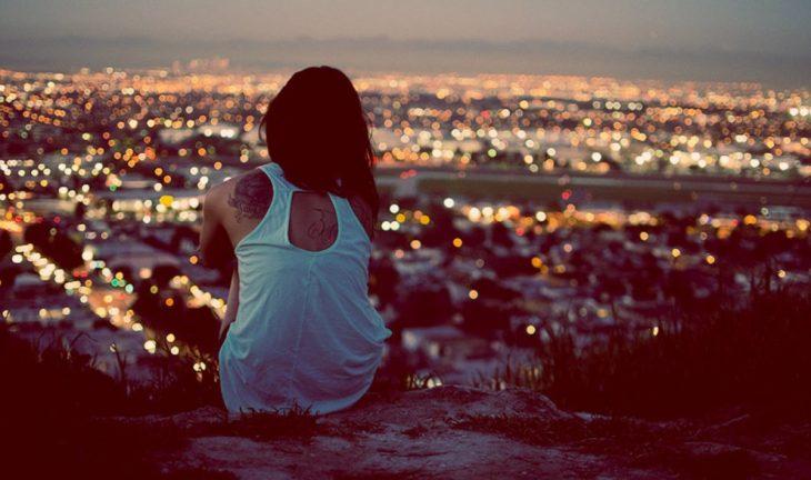 chica sentada observando la ciudad